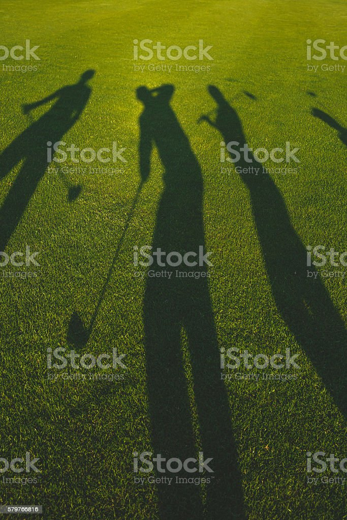golfers silhouette on grass stock photo