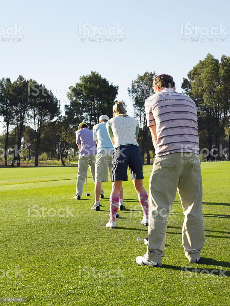 Golfers Standing In Row Teeing Off stock photo