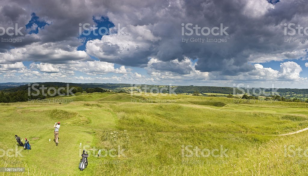 Golfer's Teeing Off on Green Under Overcast Sky royalty-free stock photo