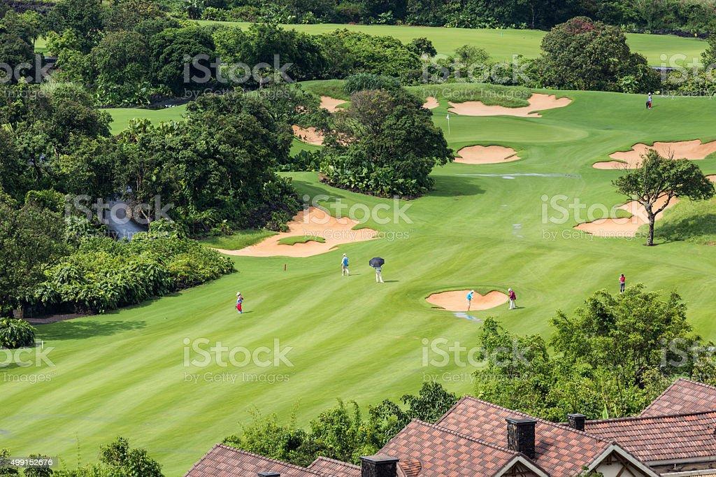golfers walking on fairway golf course stock photo