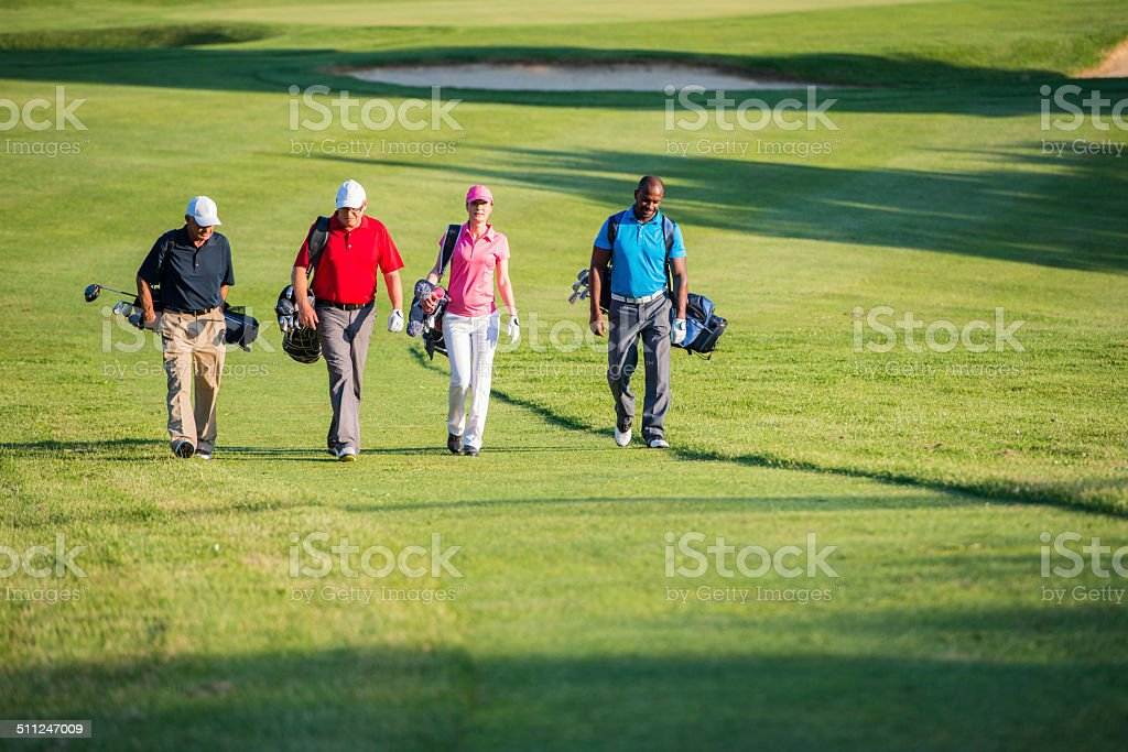 Golfers Walking On The Golf Course stock photo