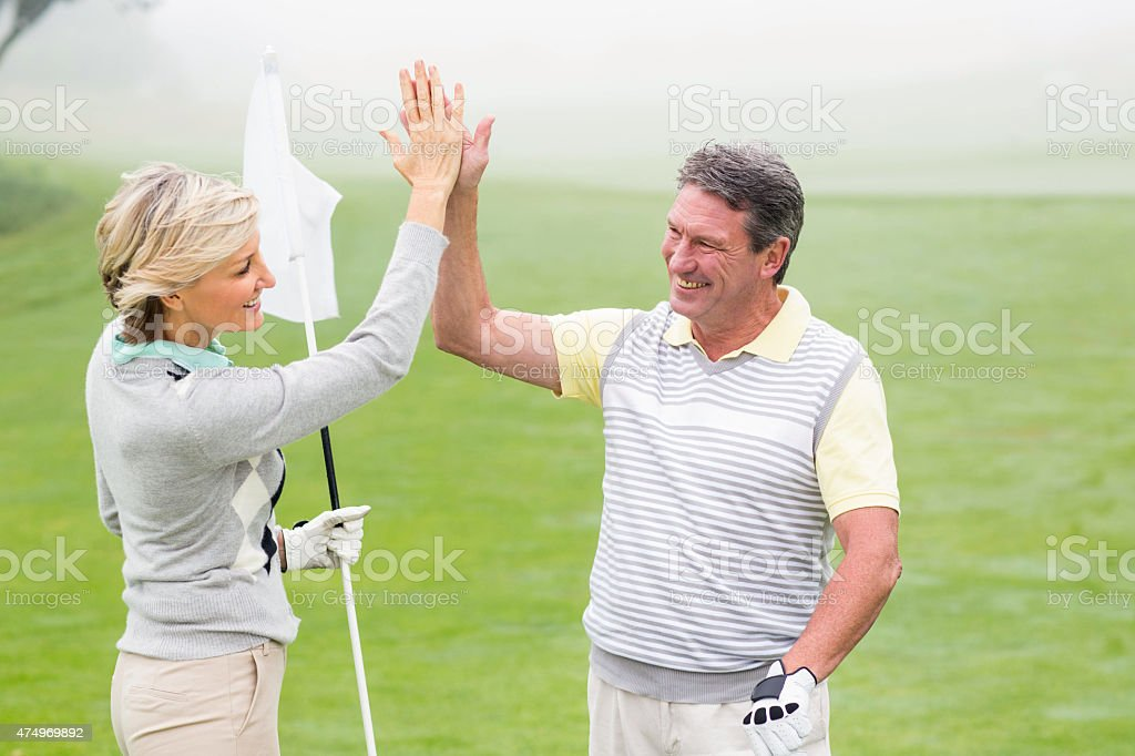 Golfing couple high fiving stock photo