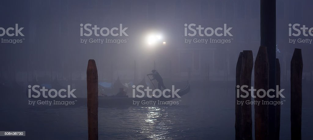 Gondola in a thick fog during nightfall in Venice stock photo