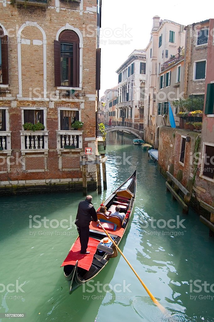 Gondola in Venice going down a small residential canal stock photo