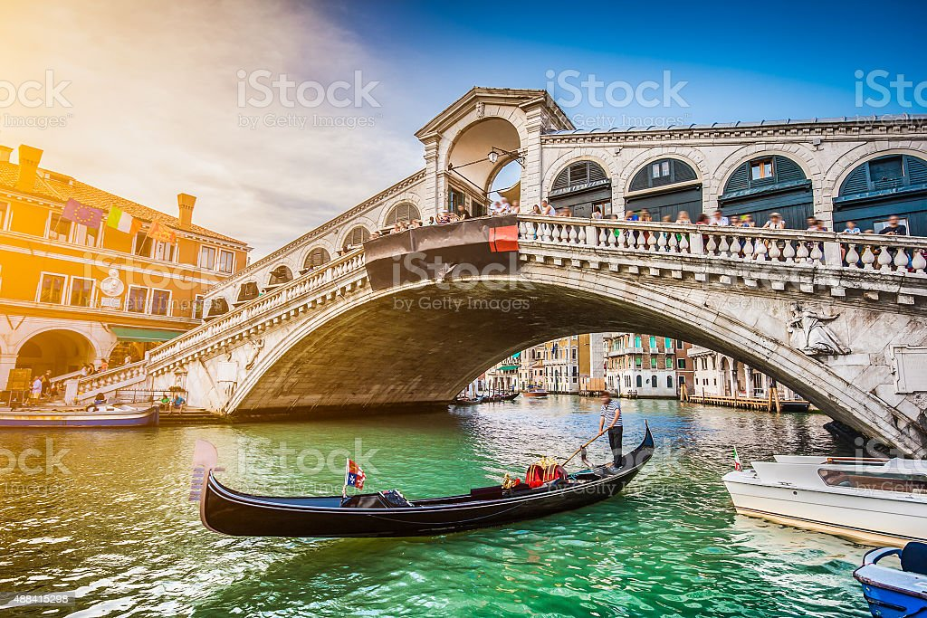 Gondola on Canal Grande with Rialto Bridge at sunset, Venice stock photo