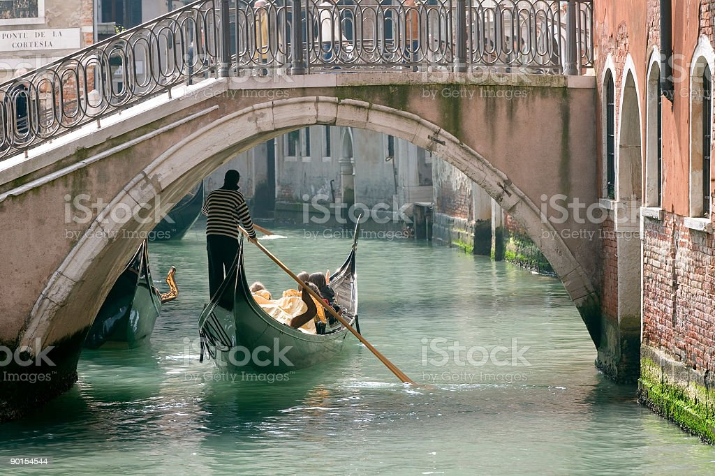 Gondola on small canal under bridge in Venice.(XXL) royalty-free stock photo