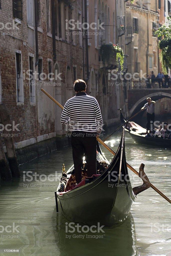Gondolier in Narrow Venetian Canal royalty-free stock photo