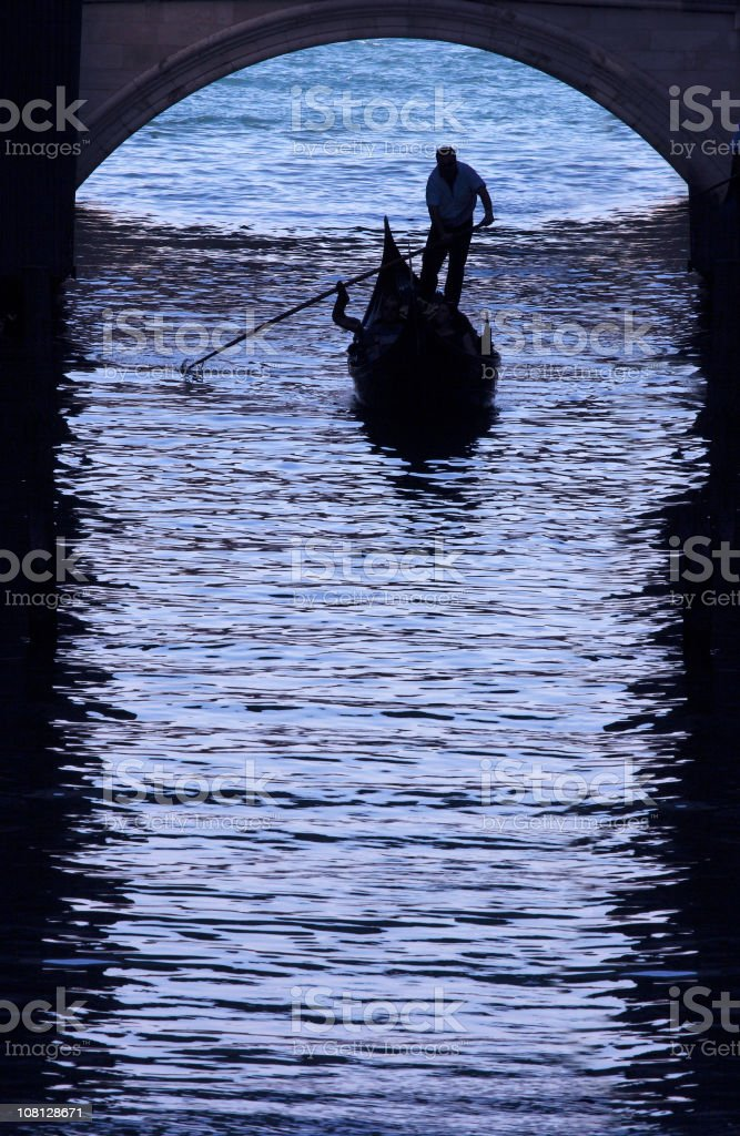 Gondolier Navigating Gondola Under Archway in Venice Canal stock photo