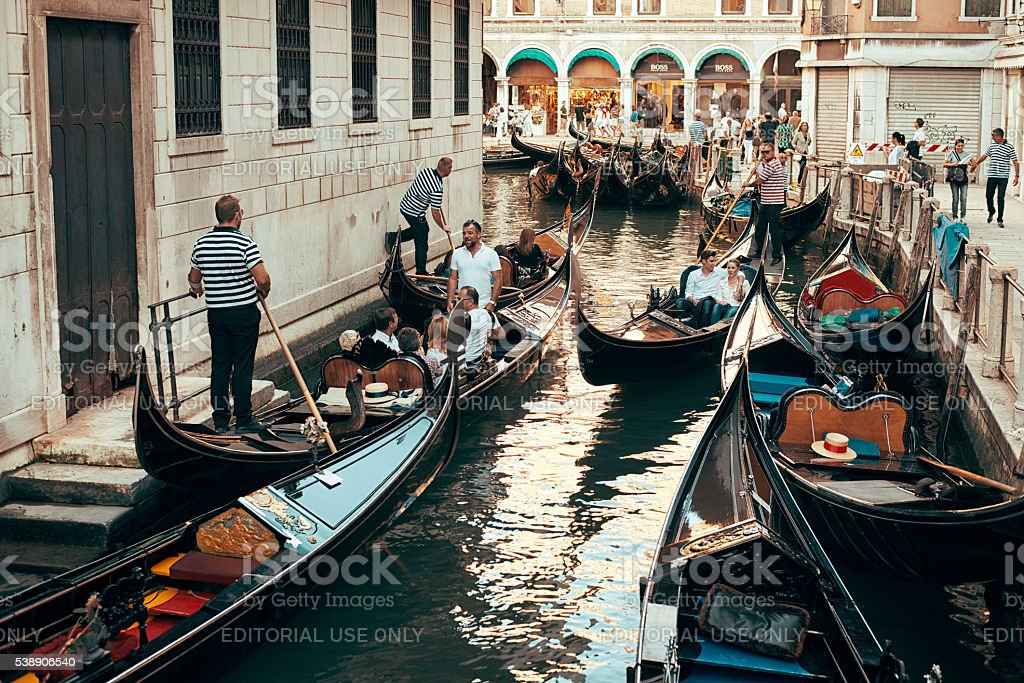 Gondolier ride tourists on the water in Venice stock photo