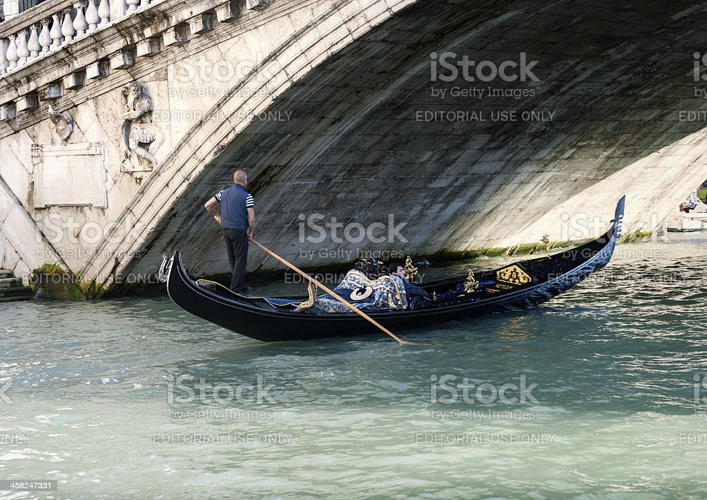 Gondolier rowing gondola with tourist on Grand Canal, Venice Italy royalty-free stock photo