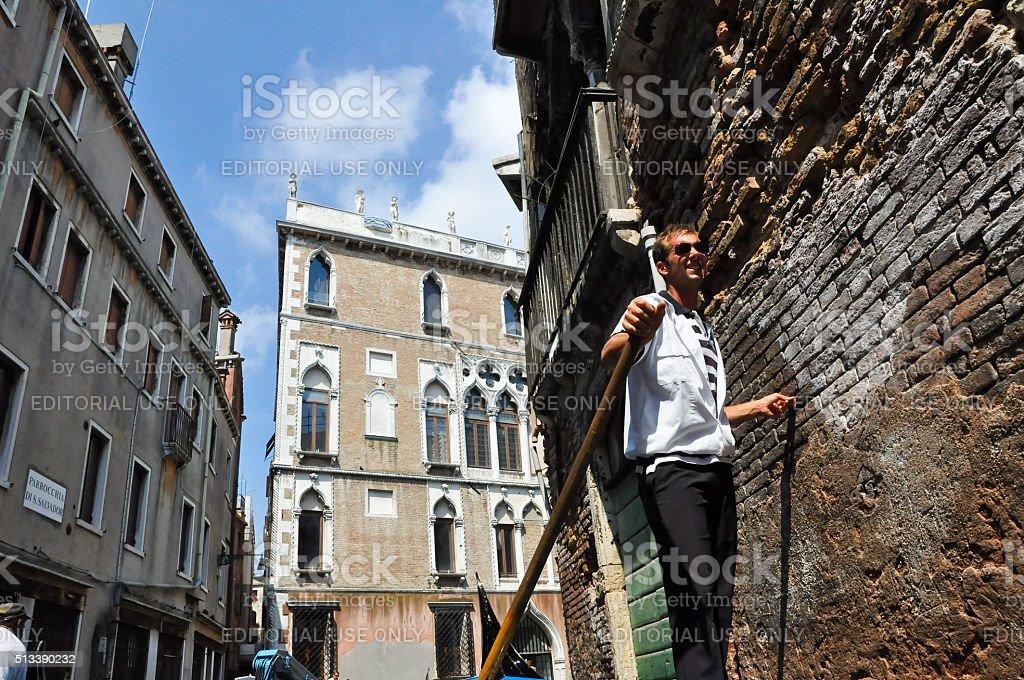 Gondolier runs the gondola on the Venetian canal in Venice. stock photo