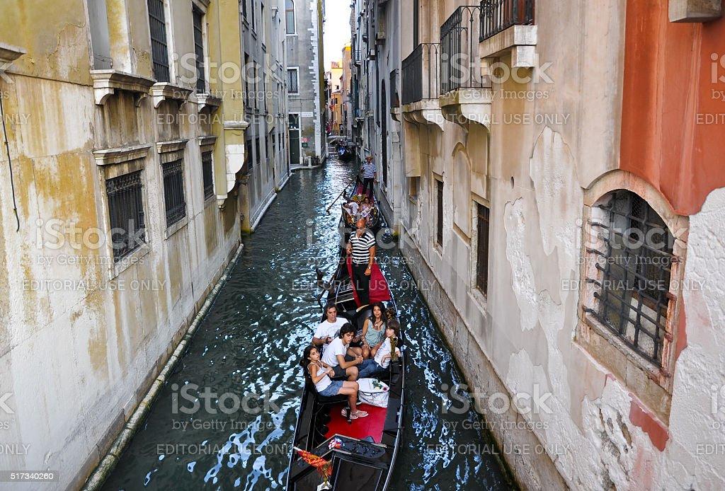 Gondolier runs the gondola with group of tourists. stock photo