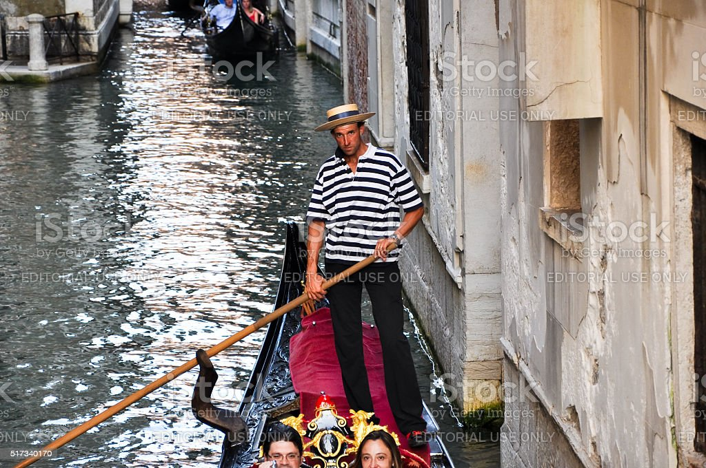Gondolier runs the gondola with the happy couple. stock photo