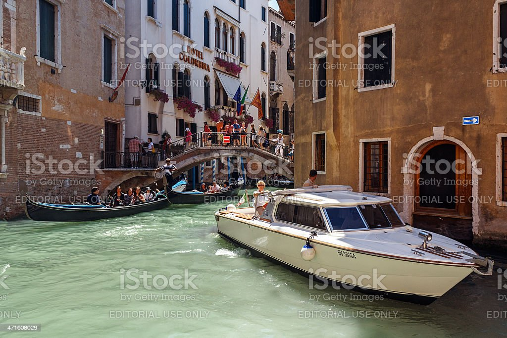 Gondolier with foreign tourists cruising a small Venetian canal royalty-free stock photo
