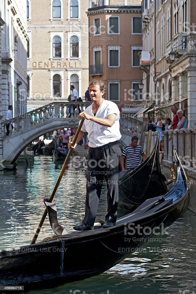 Gondoliere with his gondola in a canal of Venice, Italy royalty-free stock photo