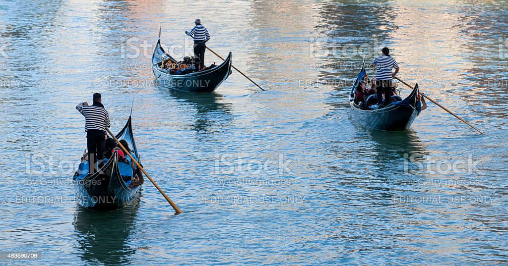 Gondoliers rowing gondolas with tourists on Grand Canal, Venice Italy royalty-free stock photo