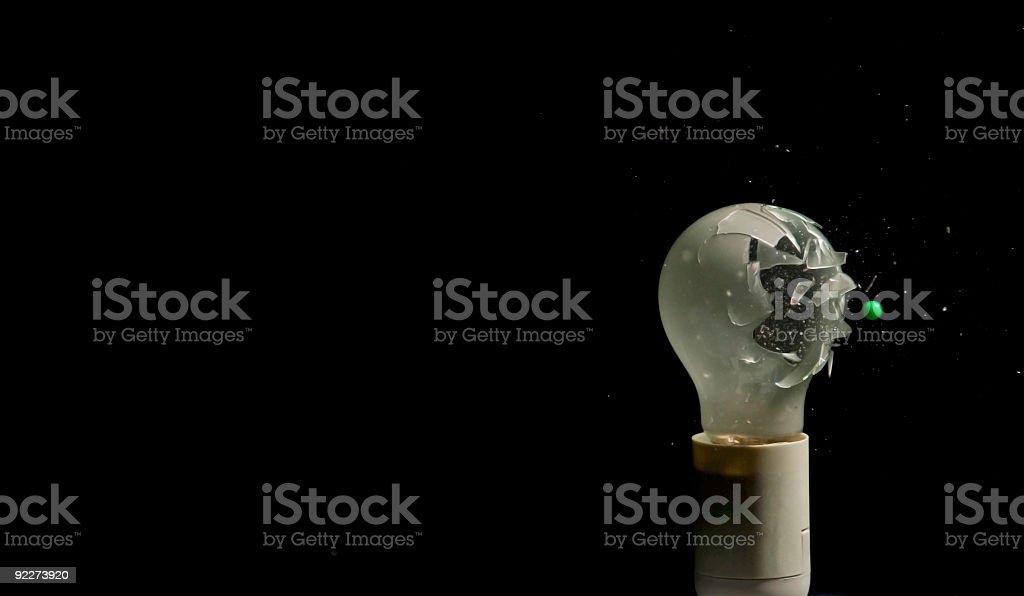 Good bye tungsten - green bullet destroys incandescent light bulb stock photo