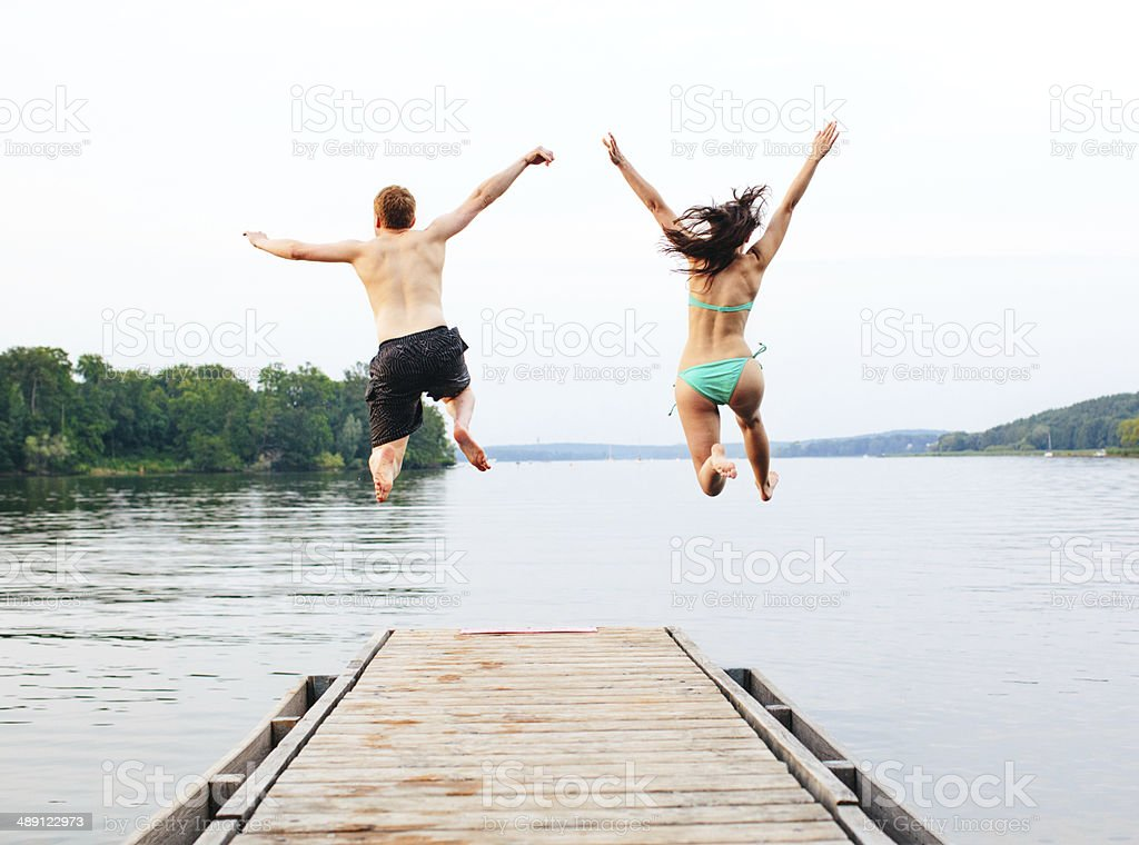 Good friends jumping into the lake stock photo