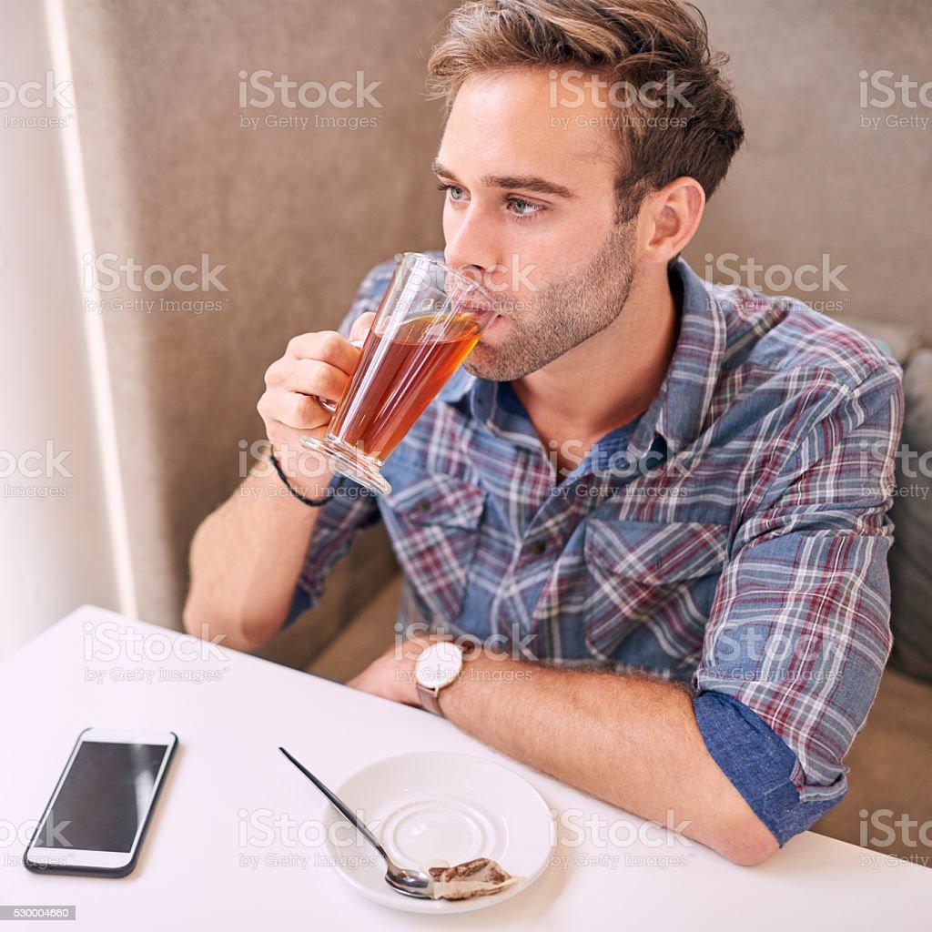 good loking man taking sip of her tea in cafe stock photo
