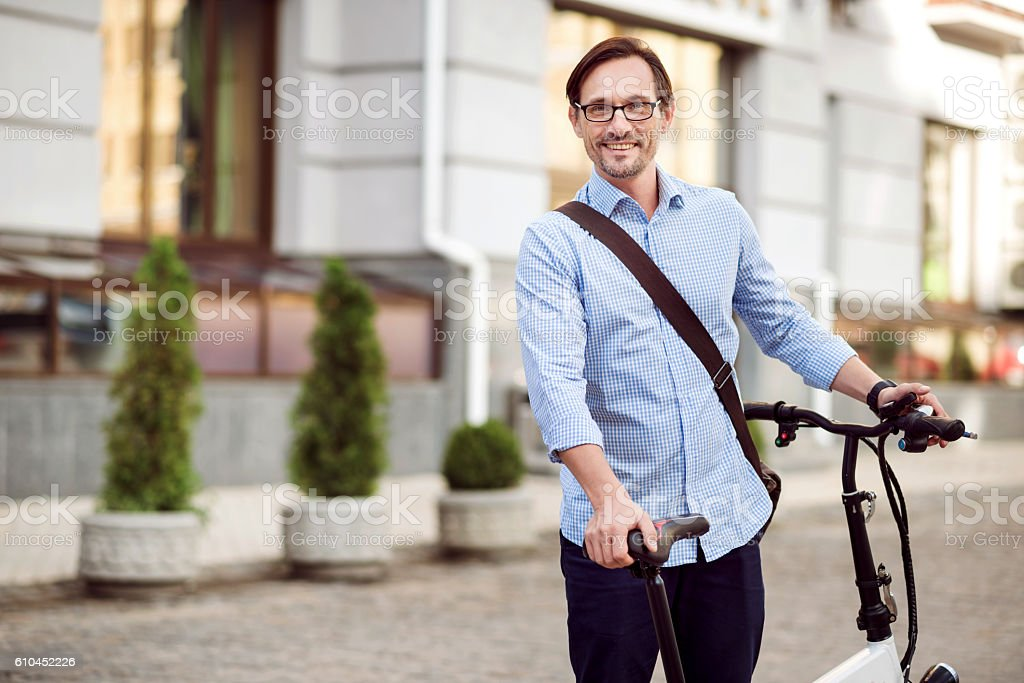 Good looking bespectacled man standing in the street. stock photo