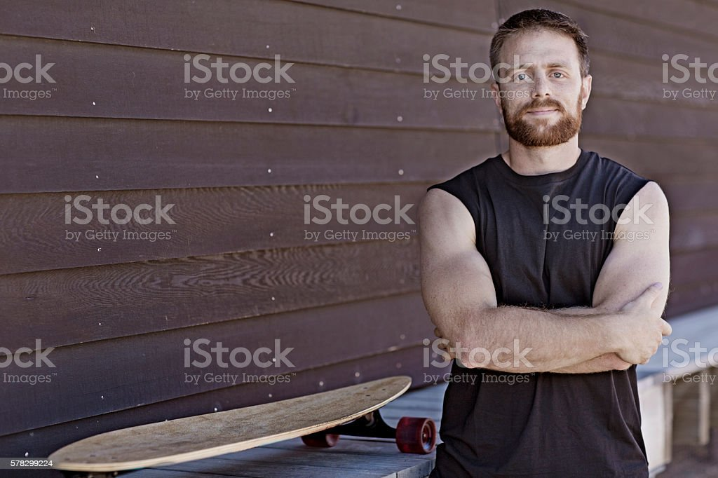 Good looking casual skateboarder male posing at summer beach location stock photo