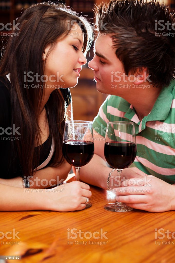Good looking couple about to kiss over glasses of wine royalty-free stock photo