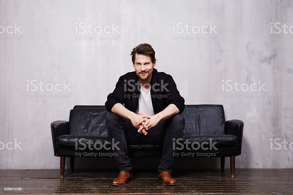 Good looking guy on sofa in portrait stock photo