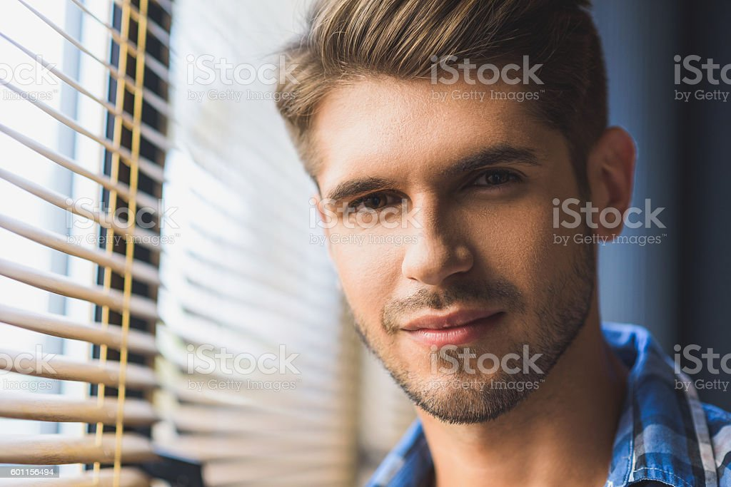 good looking man in front of a window stock photo