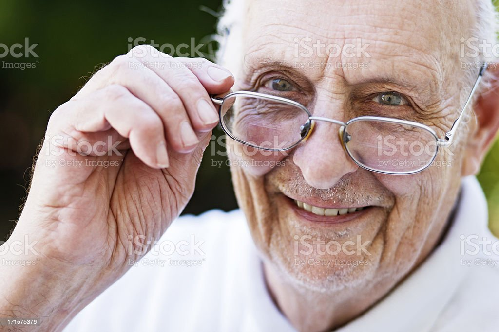 Good looking old man smiles over his glasses royalty-free stock photo