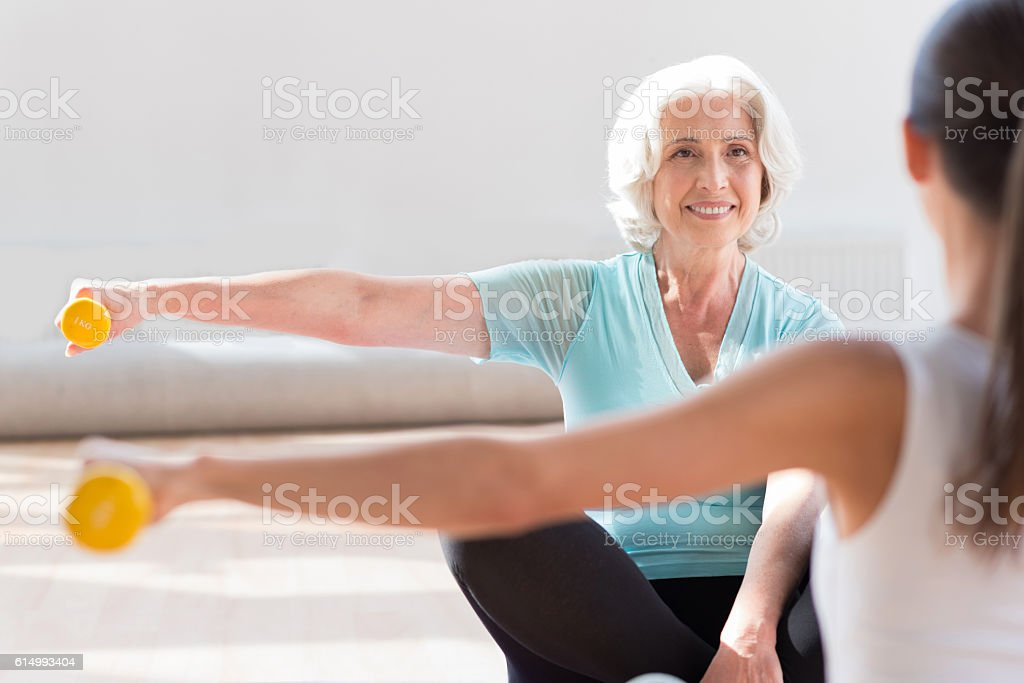 Good looking pleasant women sitting opposite each other stock photo