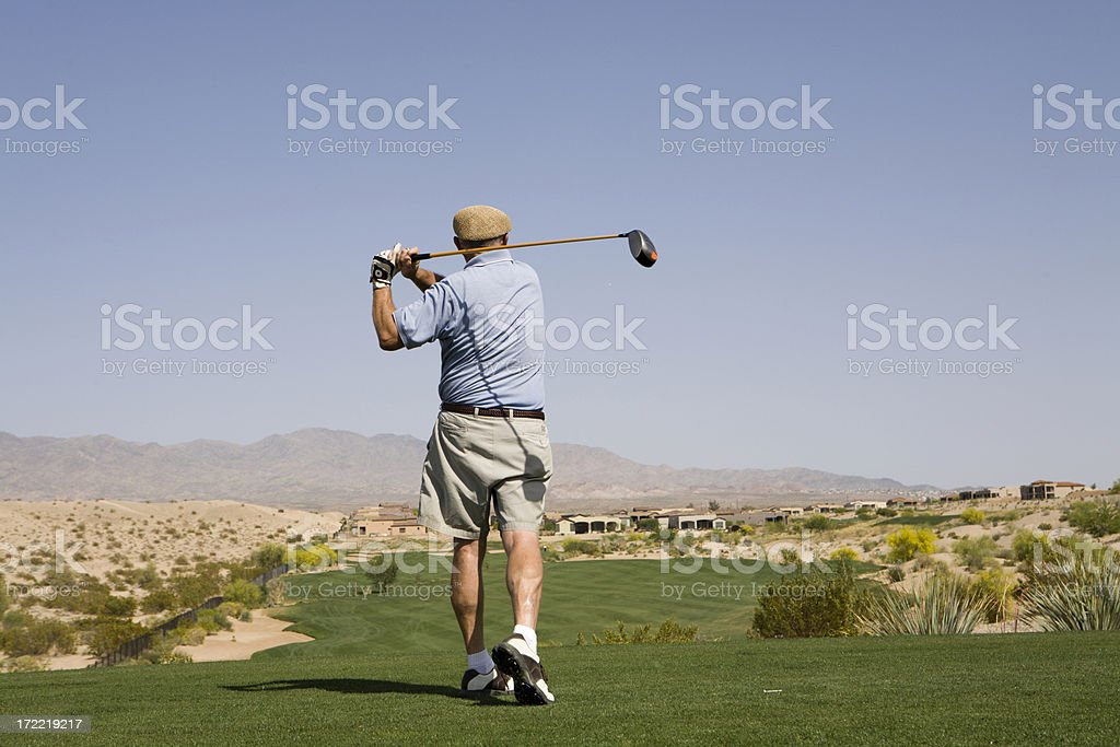 Good Looking Retired Man Hitting Ball on Golf Course royalty-free stock photo