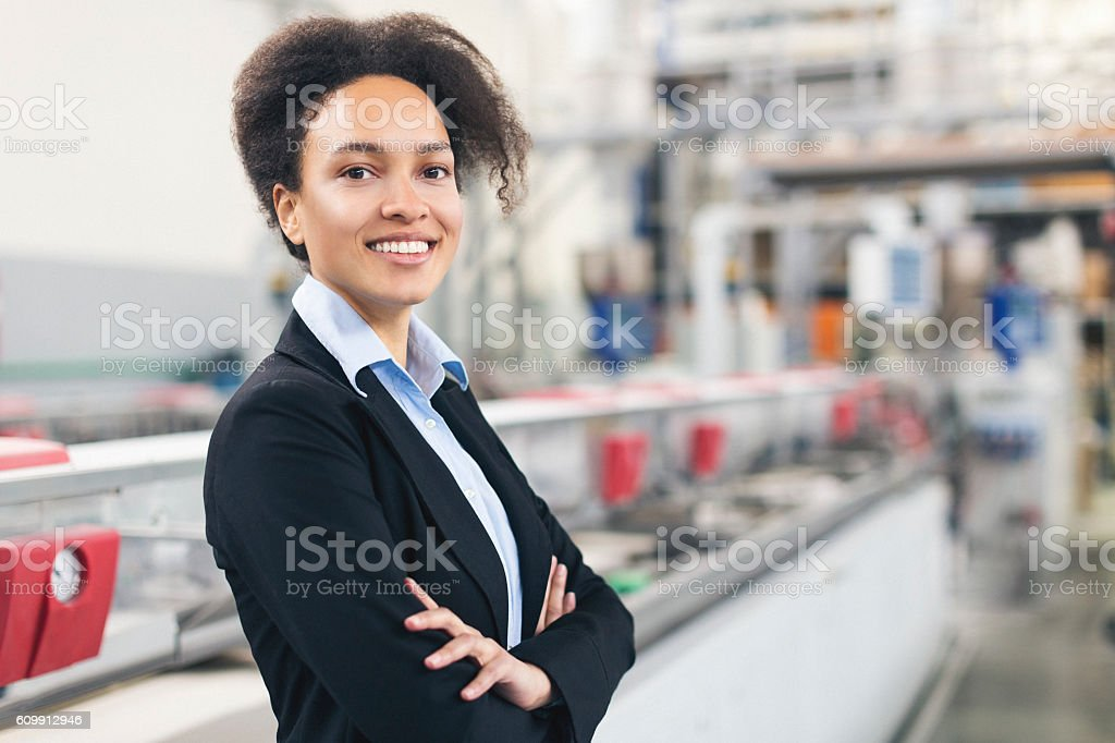 Good looking self-confident businesswoman smiling at the factory stock photo