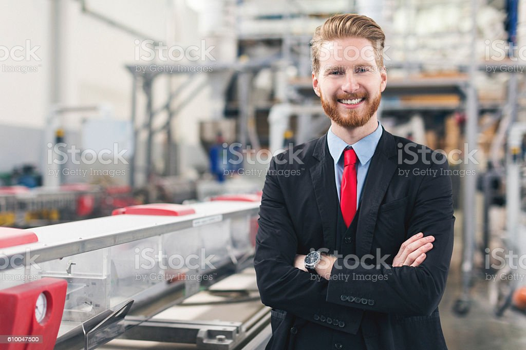 Good looking self-confident quality inspector at factory stock photo