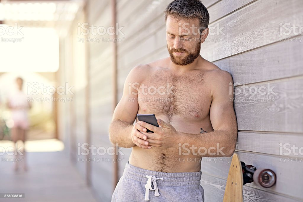Good looking shirtless male using smartphone at summer beach location stock photo