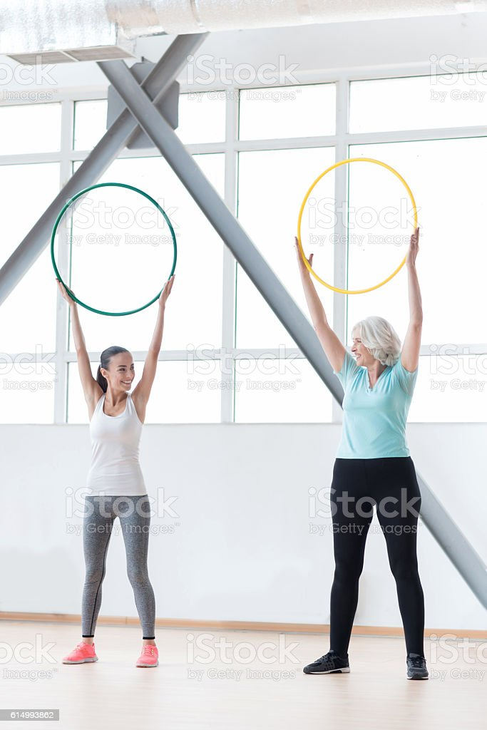 Good looking sporty women holding hula hoops stock photo