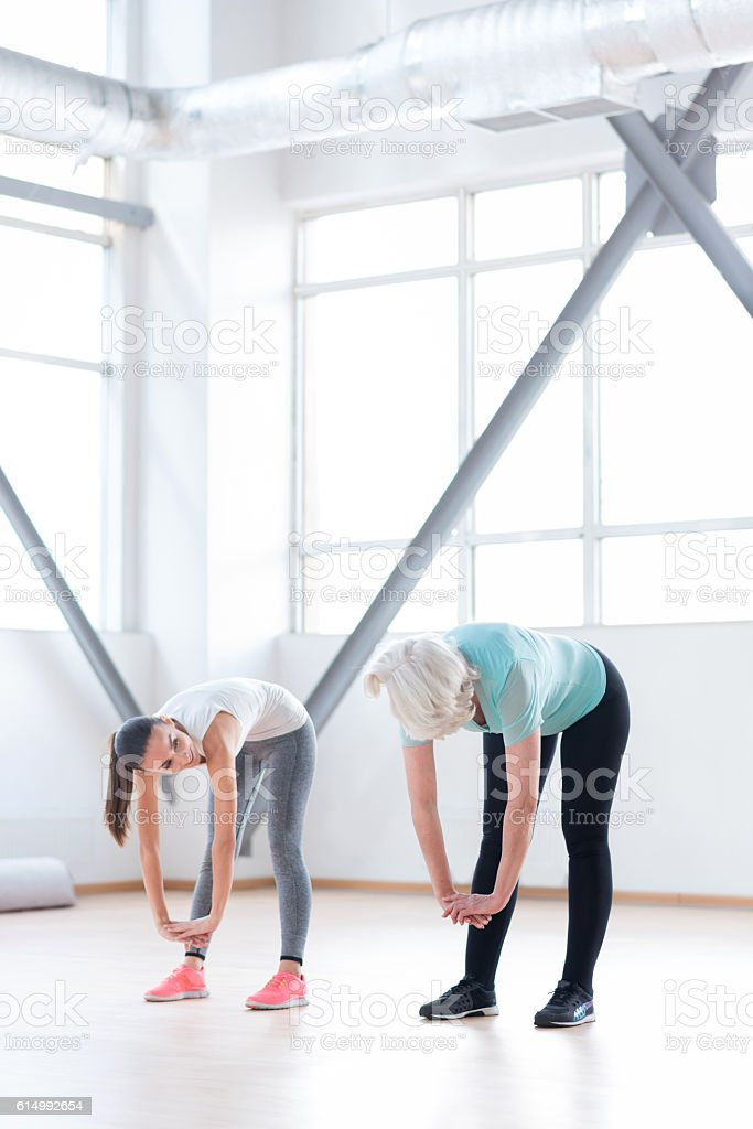 Good looking well built women trying to reach the floor stock photo