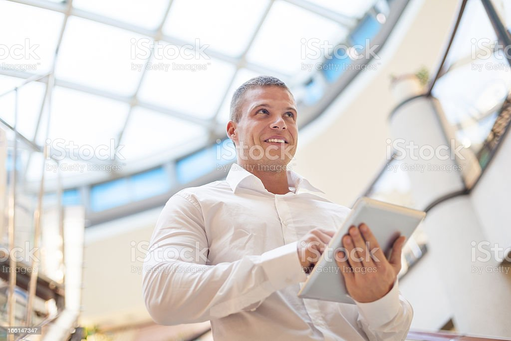 Good looking Young Businessman with tablet computer in modern bu stock photo