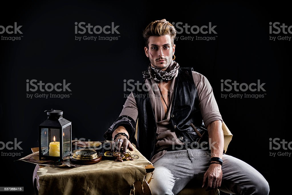 Good Looking Young Man in Pirate Fashion Outfit Sitting next stock photo