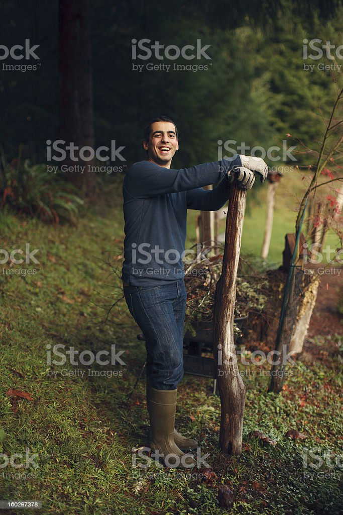Good Looking Young Man Leaning on Post While Doing Yardwork stock photo