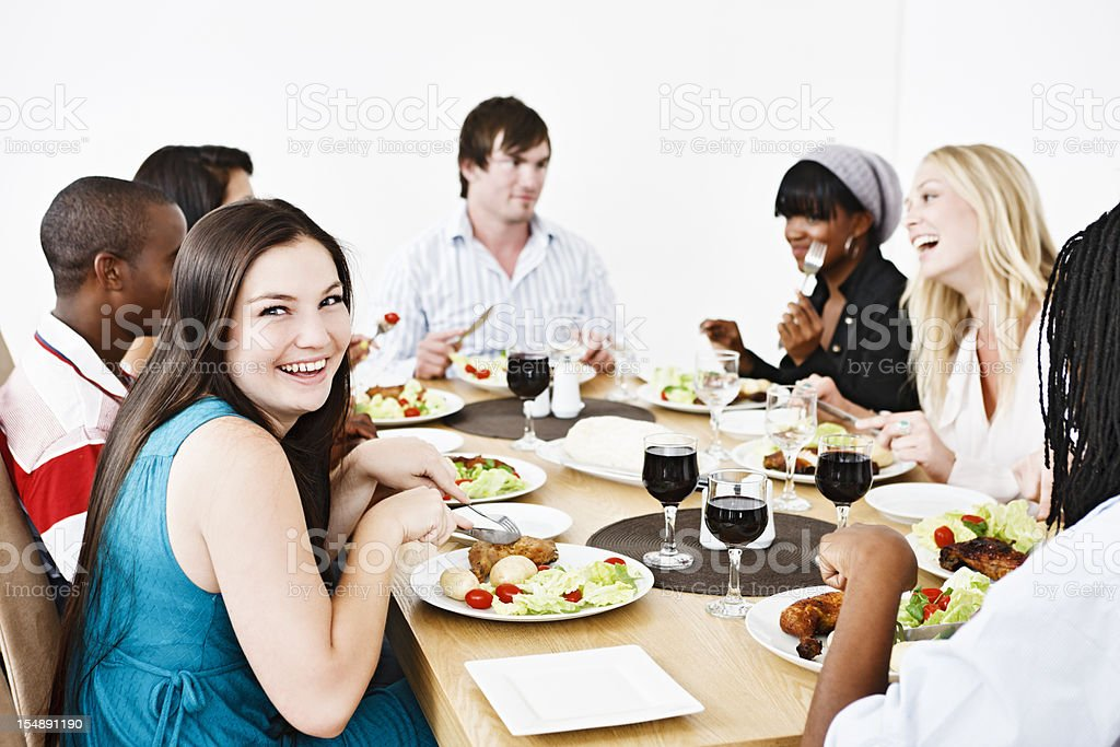 Good looking young people enjoying eating together, smiling royalty-free stock photo