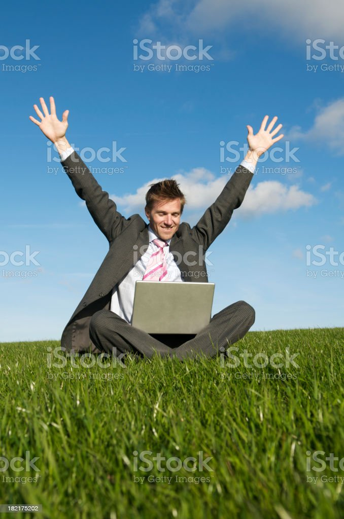 Good News Businessman Sitting in Meadow and Celebrating with Laptop royalty-free stock photo