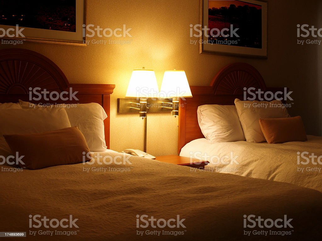\'Hotel room with 2 beds, warm light from wall lamps.\'