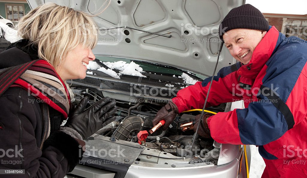 Good Samaritan giving a stranded woman's car a jump start stock photo