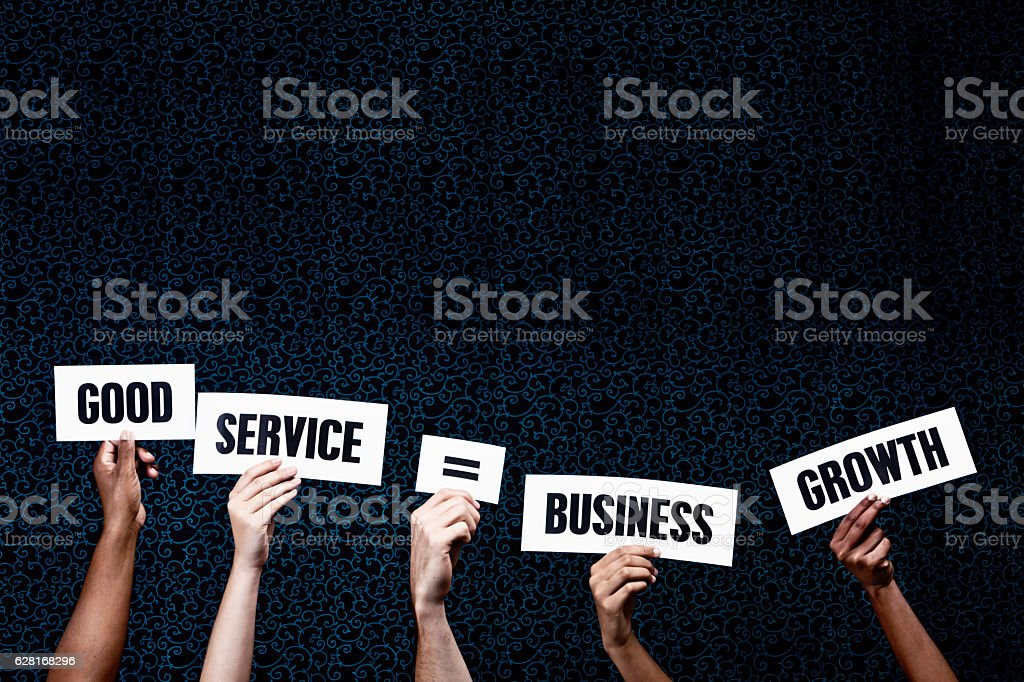 'Good service = Business Growth' say hand-held words stock photo