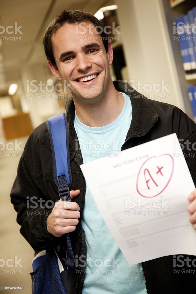 Good Student Holding Out A+ Grade on Exam Paper royalty-free stock photo