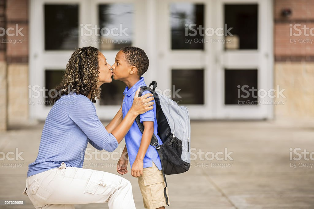 Goodbye. Little boy kisses mom on first day of school. stock photo