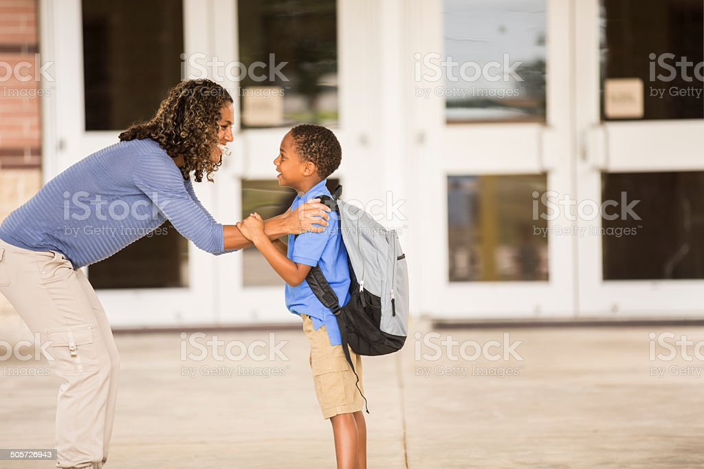 Goodbye mom. Little boy on his first day of school. stock photo