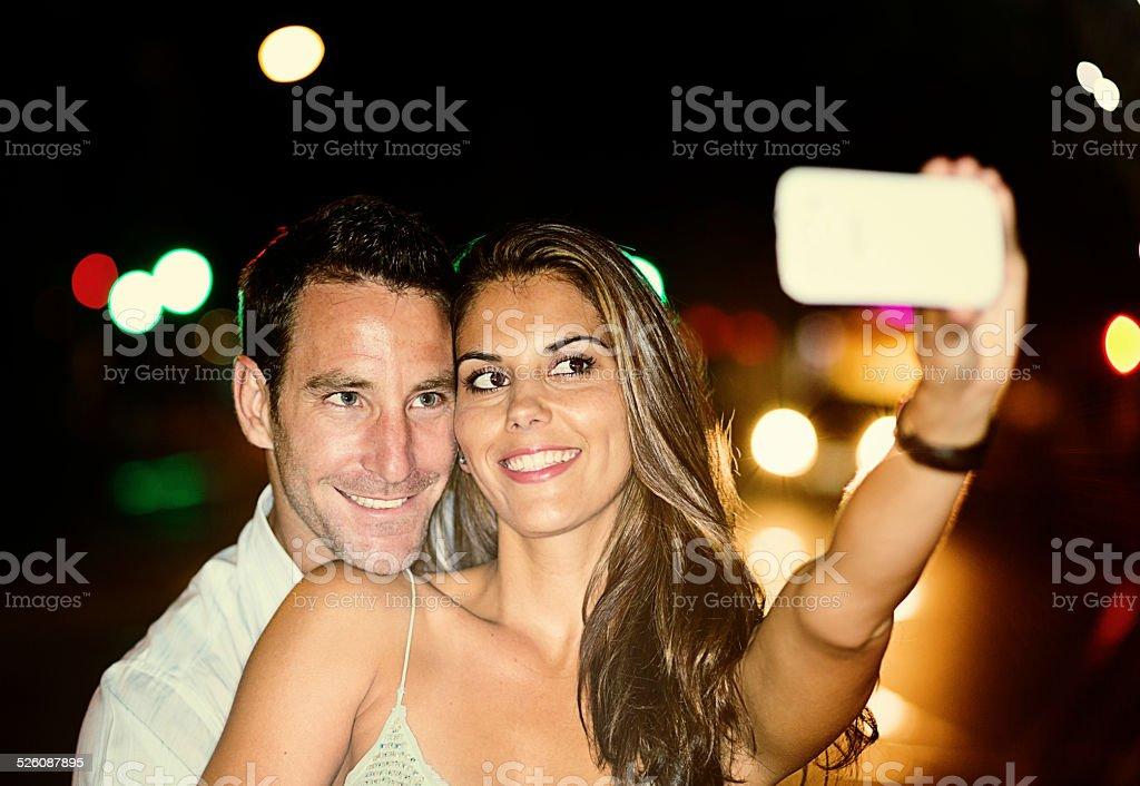 Good-looking couple in nighttime street take smiling selfie stock photo
