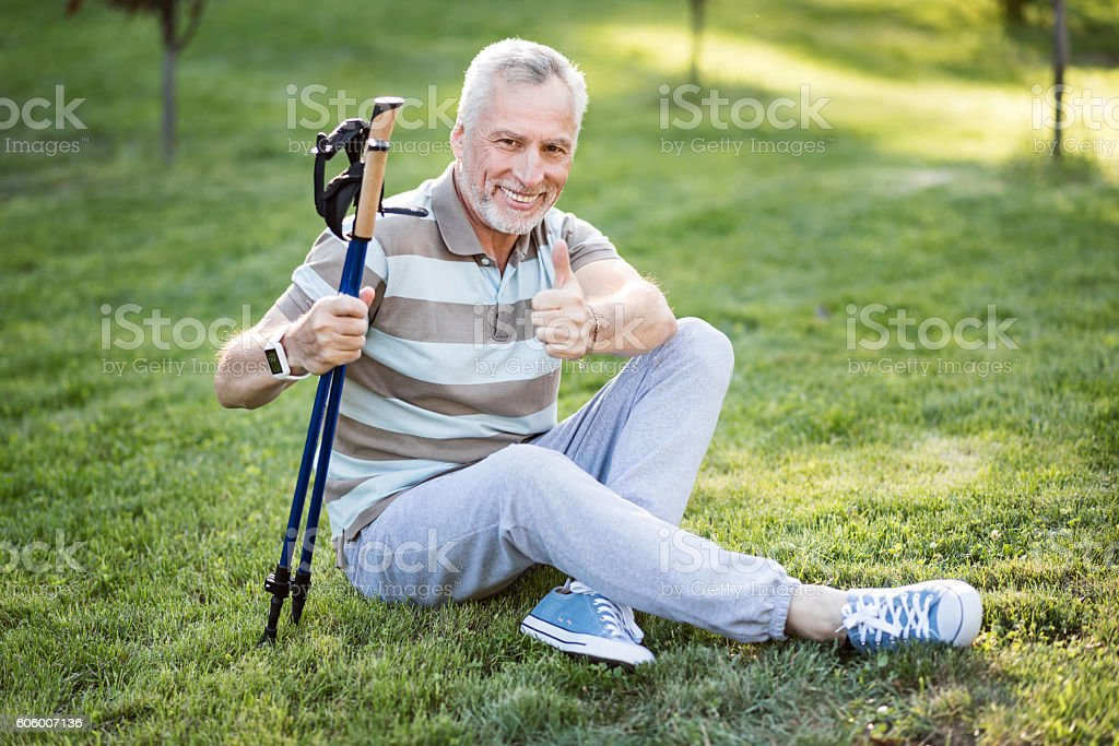 Good-looking old man sitting on grass with his legs stock photo
