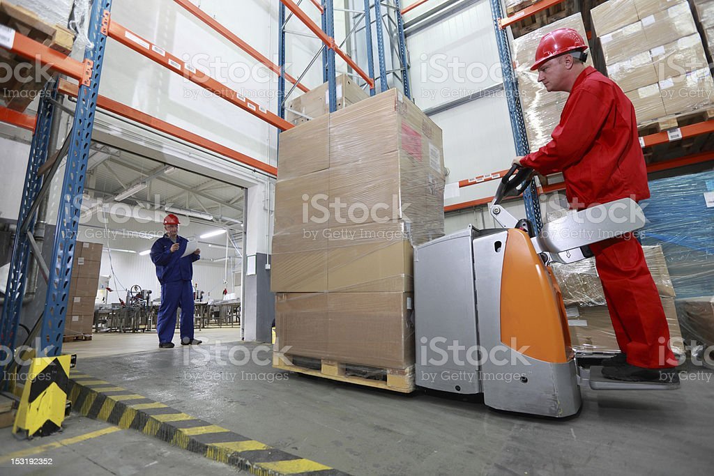 Goods delivery - two workers working in storehouse stock photo